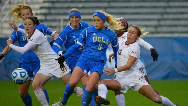 A 2013 photo of UCLA in action against Florida State. It includes, from left, Sam Mewis (22), Megan Oyster (21) and defender Abby Dahlkemper (8).