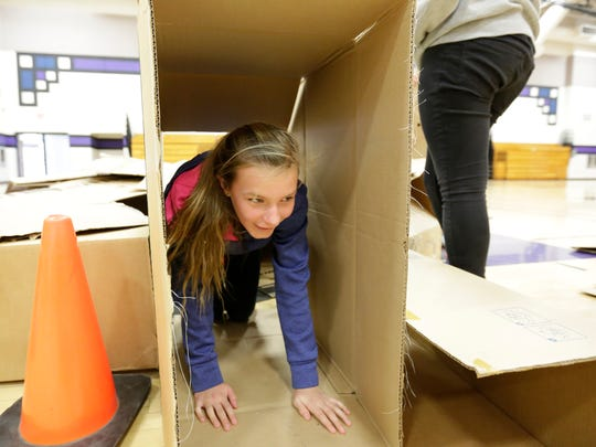 Seventh-grade student Lydia Ellis crawls in a paper cardboard shelter she built Friday, January 29, 2016, at Mosinee Middle School.