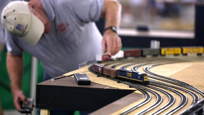 A model railroad engineer adds cars to his train.