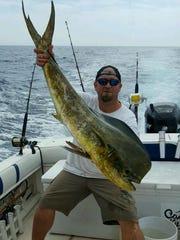 Eric Mackinnon shows off a great mahi catch.