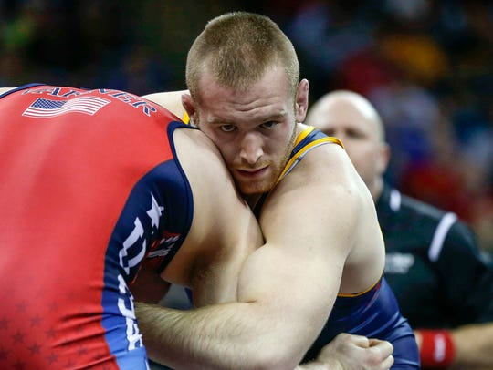 Kyle Snyder squeezes the upper body of Jake Varner