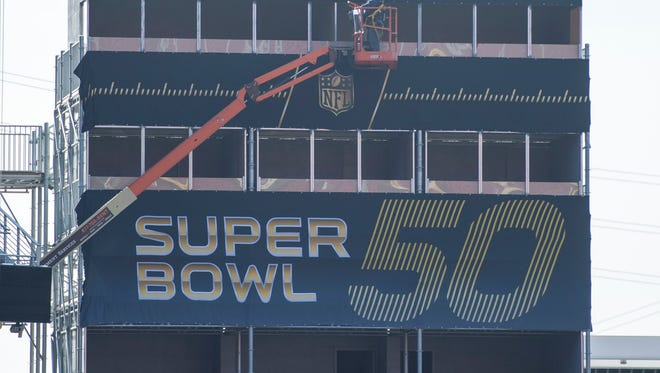 A worker works on a temporary structure inside the stadium during a field preparation press conference prior to Super Bowl 50 at Levi's Stadium.