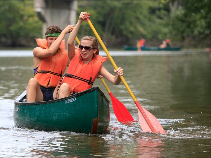 Maggie Weighner and other members of the St. Francis of Assisi Newman Center launch from Morrow's Meadow in dozens of canoes and kayaks for a trip down the White River on Monday. Many had never been down the river in a boat before.