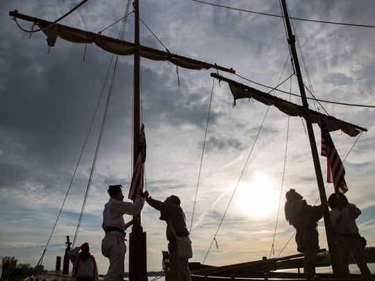 Reenactors in the Lewis and Clark expedition take down the American Flags from their ships once they dock in Henderson, Ky., on Monday evening.