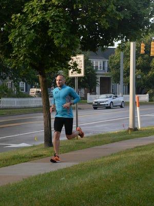 Bradley Koback runs along Maple, west of downtown Birmingham.