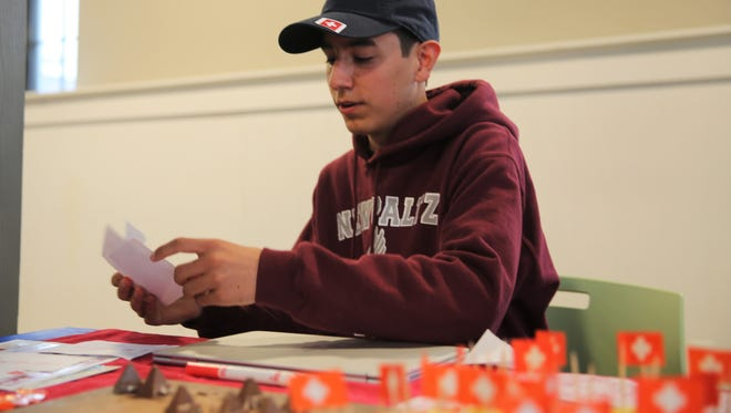 Timon Gloor lays out some cards on his table. The native of Switzerland has attended New Paltz High School for the academic year.