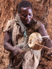 A bushman plays for visitors inside a baobab tree.