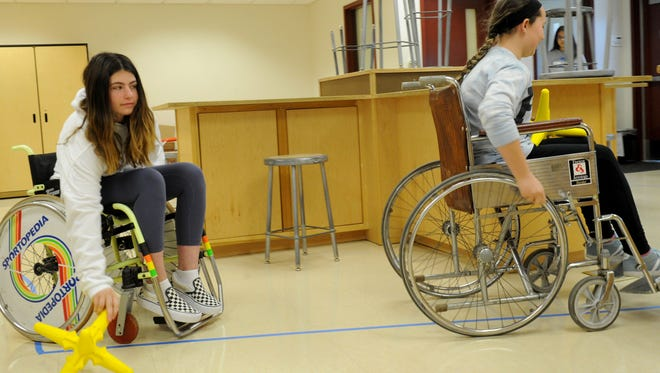 Charlotte Smith, left, and Maya Dennis, both seventh graders from Lindero Canyon Middle School in Agoura Hills, pick up objects while seated in wheelchairs during an Ability Awareness Fair. The students rotated among different stations so they could experience what life would be like with communication, reasoning, fine motor, mobility or vision challenges.