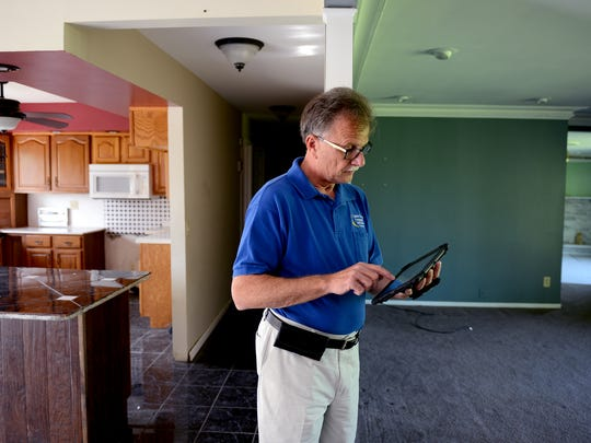 Eaton County Treasurer Bob Robinson pulls up information on tax-foreclosed homes in the county on his tablet as he walks through a foreclosed home May 27 in Dimondale. The home will be auctioned off by the county in September.