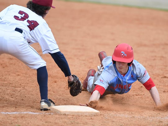 Gibson County's Camron McMackin slides to first base as Madison's Bryce Pearson reaches to tag him during their game, Monday, March 26.
