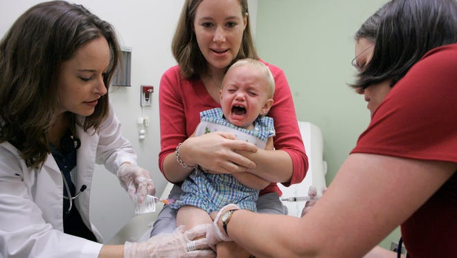Duncan Barnes, 1, is held by his mother, Jennifer Barnes, while receiving a vaccine for swine flu from Dr. Susan Henderson, left, and a vaccine for seasonal flu from nurse Allison Ross at Emory Children's Center in Atlanta in 2009.