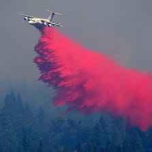 POLLOCK PINES, CA - SEPTEMBER 17:  An air tanker drops Foscheck fire retardant on a hillside ahead of the King Fire on September 17, 2014 in Pollock Pines, California. The King fire is threatening over 1,600 homes in the forested area about an hour east of Sacramento and has consumed over 18,544 acres. The out of control fire is 5 percent contained.