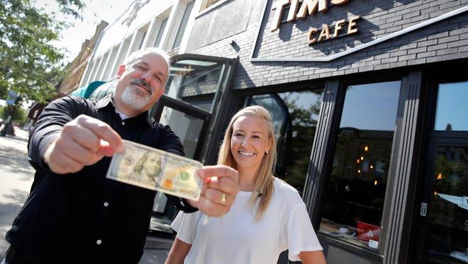 Dan Higgins, with USA TODAY NETWORK-Wisconsin, holds a $100 bill on Aug. 25 as he and Molly Lucas, a food Instagrammer, begin their journey through the Fox Cities at Timshel Cafe in Neenah for USA TODAY's Travel Allowance series.