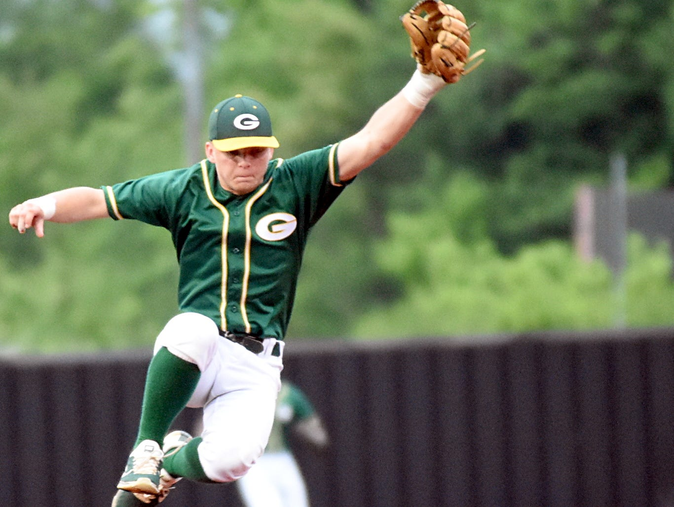 Gallatin High senior shortstop James Rockwell makes a leaping attempt to catch a first-inning throw as Wilson Central senior leadoff hitter Drew Trice slides safely into second base with a stolen base.