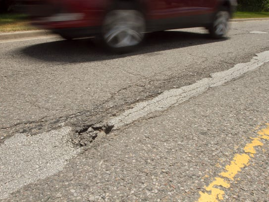 A passing car misses a hole on Spencer Road Tuesday,