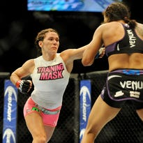 Sep 27, 2014; Las Vegas, NV, USA; Amanda Nunes (blue gloves) fights Cat Zingano (red gloves) during a bantamweight fight in UFC 178 at MGM Grand Garden Arena. Mandatory Credit: Stephen R. Sylvanie-USA TODAY Sports