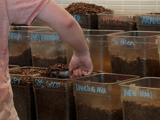 Adam Lange scoops coffee beans before making a drink at a Philz Coffee shop in San Francisco.