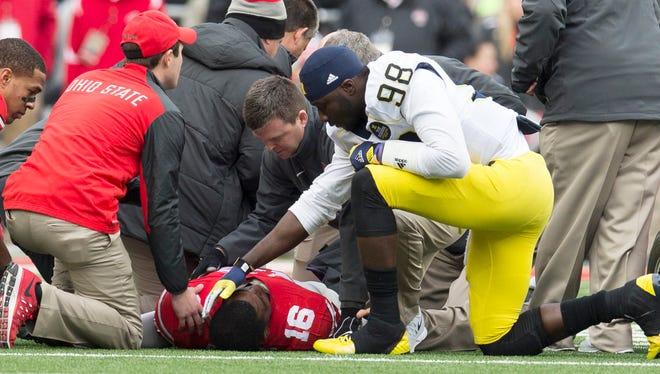 Nov 29, 2014; Columbus, OH, USA; Michigan Wolverines quarterback Devin Gardner (98) checks on Ohio State Buckeyes quarterback J.T. Barrett (16) after Barret was injured at Ohio Stadium. Mandatory Credit: Greg Bartram-USA TODAY Sports