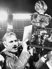 University if Miami coach Howard Schnellenberger holds the 1981 Peach Bowl trophy aloft after his team, led by quarterback Jim Kelly, defeated Virginia Tech, 20-10.