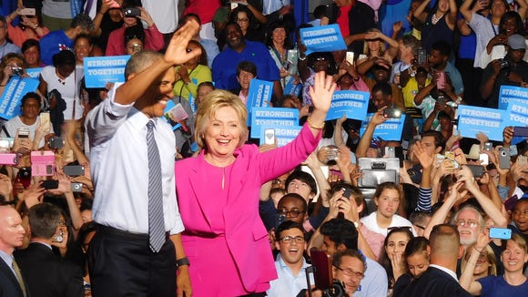 President Barack Obama and Hillary Clinton wave at a campaign rally in July in Charlotte.