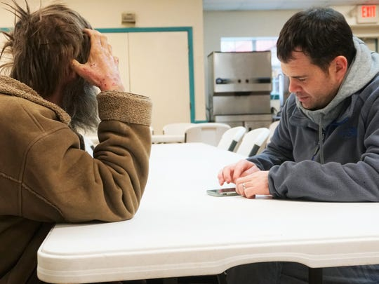Kyle Knutson, lead case manager at the Salvation Army of the Coastal Bend, fills out a Point in Time count survey while talking with a homeless man at the shelter on Thursday, Jan. 25.