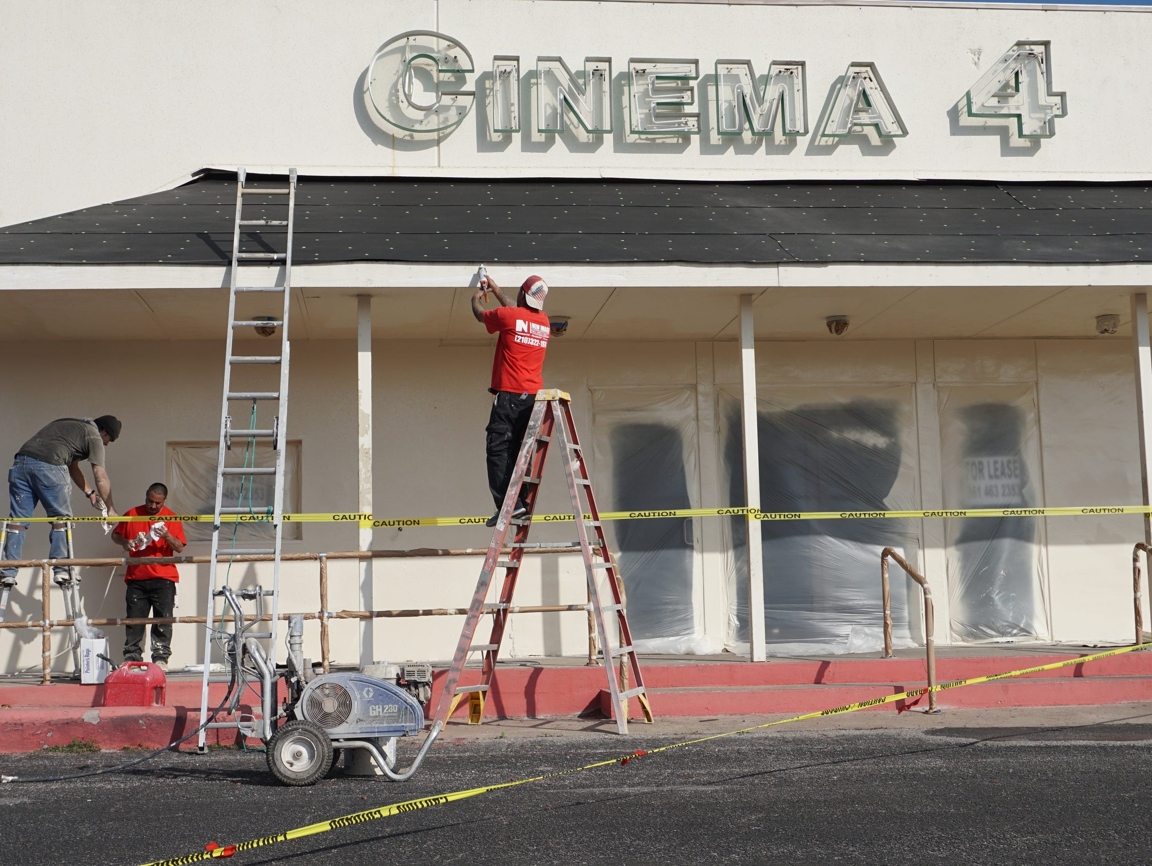 Workers paint the outside of the shopping strip housing