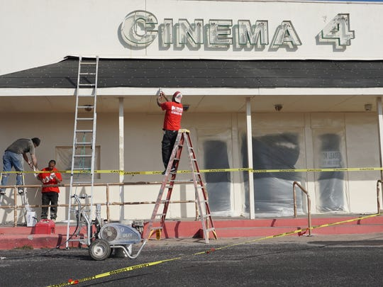 Workers paint the outside of the shopping strip housing the Cinema 4 movie theater in Rockport on Monday, Feb. 19, 2018. The theater will not reopen post-Harvey, owner Jeff Dinger said.