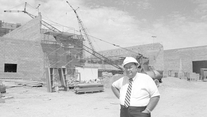 In the then image, taken by Spectrum photographer Nancy Rhodes in August of 1986, Sherman Bennett stands in front of the Cox Auditorium, then under construction as work progresses on Burns Arena, the west wall of which can be seen behind Bennett as well, and the rest of the old Dixie Center in St. George. A dozen years later, in 1998, the Dixie Center moved to its new location near Interstate 15's Exit 5. The Cox Auditorium and the rest of the buildings that comprised the old Dixie Center became part of the Dixie State University campus. The now image, taken by Spectrum photographer Jud Burkett shows what the completed Cox Auditorium now looks like and also shows the relatively recently added semi-permanent tent structure that has been erected south of the building.