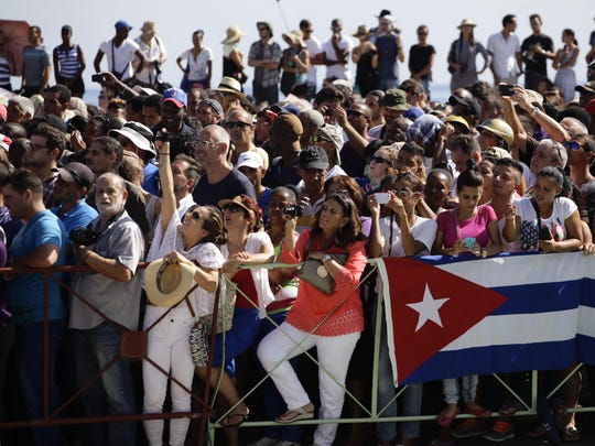 A crowd waits behind barrier with a draped Cuban national flag, near the newly opened U.S. Embassy, to catch a glimpse of the flag raising ceremony, in Havana, Cuba, Friday.