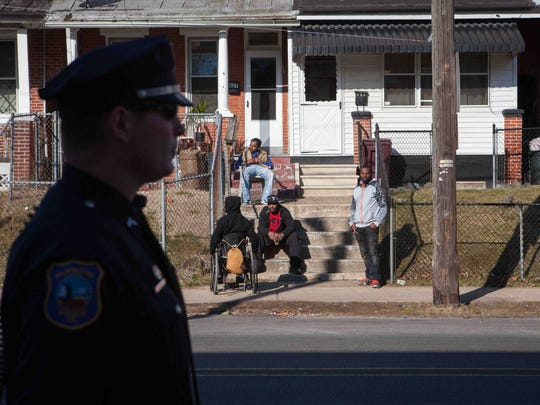 Residents look on as Cpl. Devon Jones patrols along East 22nd Street in Wilmington as part of Operation Disrupt on March 17. Officers were pulled from specialized units, such as community policing, vice, communications and internal affairs for the new program.