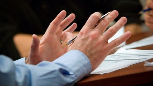 Businessman using his hands to speak in meeting.
