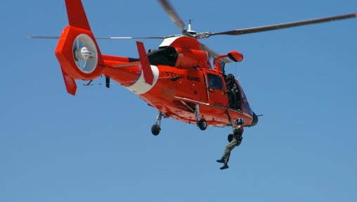 An HH-65C Dolphin demonstrates a helicopter rescue.