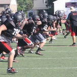 A Churchill receiver attempts to reel in a pass during Friday morning's practice.