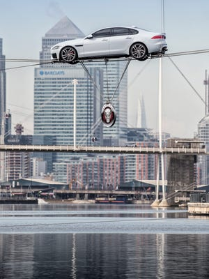 Stunt driver Jim Dowdell takes the aluminum-body 2016 Jaguar XF sedan, going on sale late 2015, 787-ft. across Royal Dock in London's Canary Wharf on two high wires to publicize the redesigned car.