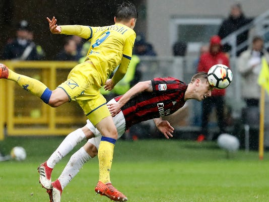 AC Milan's Lucas Biglia, right, challenges for the ball with Chievo's Mariusz Stepinski during the Serie A soccer match between AC Milan and Chievo Verona at the San Siro stadium in Milan, Italy, Sunday, March 18, 2018. (AP Photo/Antonio Calanni)