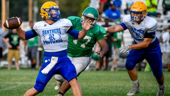 Riverside quarterback Stone Frost (4) prepares to pass to a teammate while Bolivar's Xavier Dickerson (77) moves in to tackle in a TSSAA high school football scrimmage game between Bolivar High School and Riverside High School at Bolivar Central High School in Bolivar, Tenn., Tuesday, July 31, 2018.
