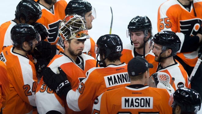 Flyers' Brandon Manning (23) speaks with goalie Michal Neuvirth (30) after a 1-0 loss to Washington in Game 6.