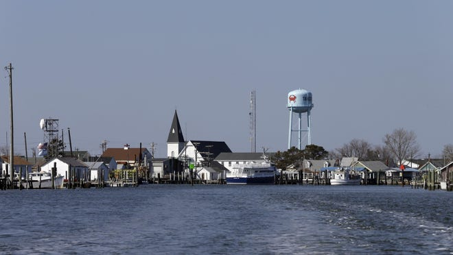 Swain Memorial Church and a water tower rise above crab shacks on the waterfront of Tangier Island, a 1,001-acre speck of land in the middle of the Chesapeake Bay.