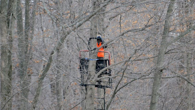A hunter uses binoculars to scan for deer in a tree stand near Oreweiler Road last year.