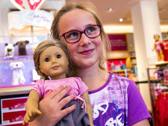"""Kate Balazs, 8, of Edmonton, Alberta, holds onto her """"Mackenzie"""" while shopping inside the American Girl Doll store in Scottsdale on Aug. 19."""