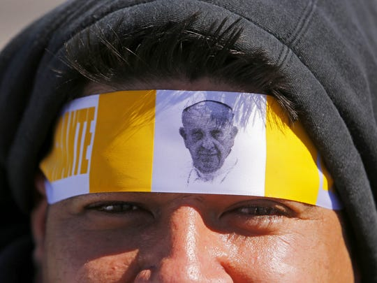 Roberto Robles wears a pope headband as he waits to