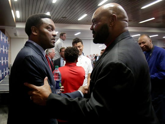 New UA head football coach Kevin Sumlin (left) greets former UA great Ricky Hunley on Tuesday.