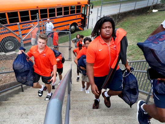 Blackman football players, with their equipment in hand, enter Braly Municipal Stadium in Florence, Ala.