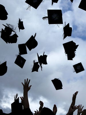 FILE: Students throw their mortarboards in the air during their graduation at the University of Birmingham degree congregations  on July 14, 2009.