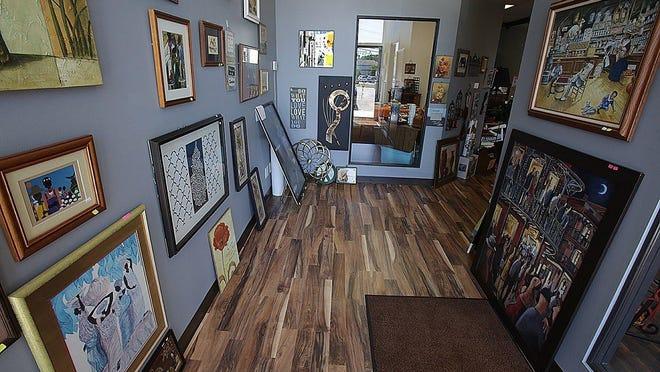 A hallway of framed art at The Thrift Chicks LLC.