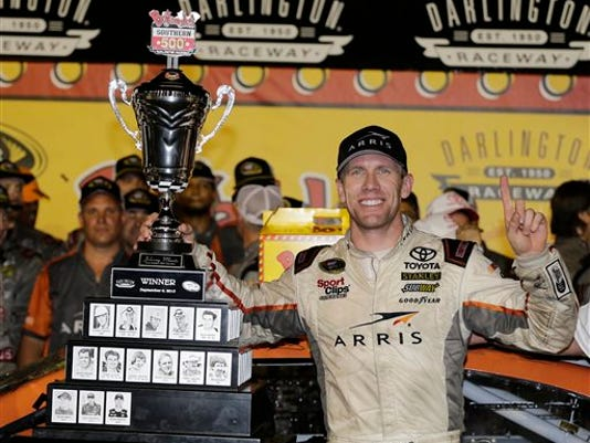 Carl Edwards celebrates in victory lane after winning a NASCAR Sprint Cup auto race at Darlington Raceway in Darlington, S.C.