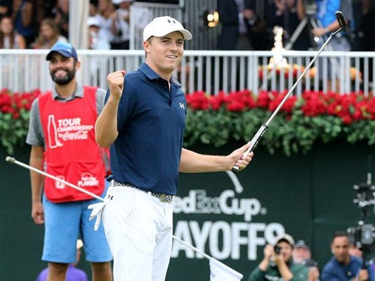 Jordan Spieth and his caddie Michael Greller react as he sinks his a putt on the 18th green to win the Tour Championship golf tournament at East Lake Golf Club on Sunday in Atlanta.