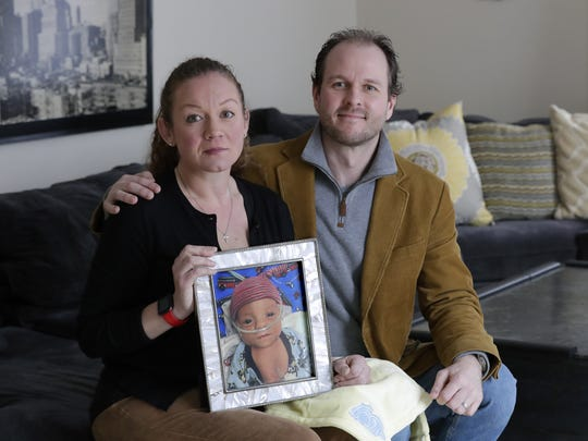 Tracy and Brian Ludka hold a photo of their son, Carson, at their home in Neenah. Carson was born premature and died at 4 months. The couple has started a program to provide special blankets to children in difficult medical situations.