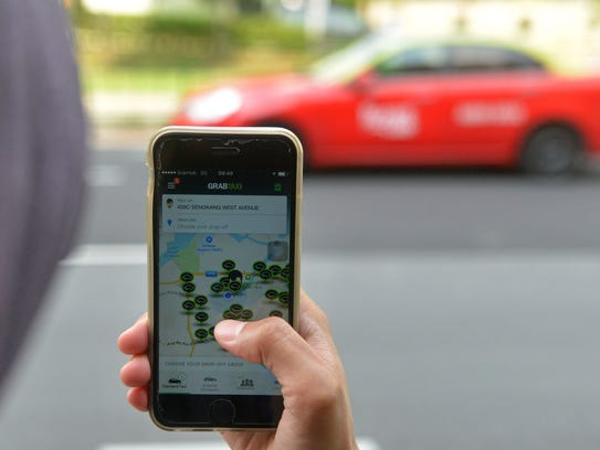 A commuter uses the smartphone app GrabTaxi, which