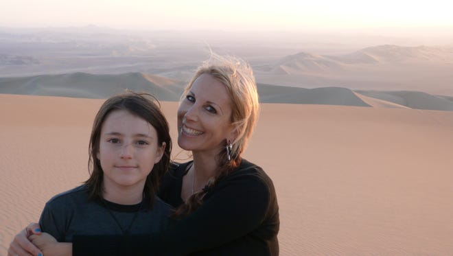 Lainie Liberti and her son, Miro, explore the sand dunes of Huacachina in southwestern Peru.